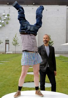 Austrian artist Erwin Wurm, right, stands next to an extra participating in the sculpture 'Hose lueften, Haende hoch' (air out pants, hands high) at the garden of the Staedel Museum, in Frankfurt - 'One Minutes Sculptures'