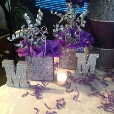 Sweet sixteen purple party decorations. Made these from gift small gift bags sprayed with adhesive and then covered with glitter, tissue paper and sparkly Christmas picks.  I covered the cardboard letters (found in the dollar bins at Michaels) with silver metallic paint and glitter.  Easy and inexpensive table decor!
