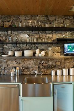 The open shelving over this rustic stone wall brings a little family charm into this already beautiful space!