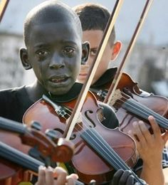 A imagem é do Brasil. O nome do menino é Diego Frazão, de Orquestra de Cordas AfroReggae. Esta foto foi tirada durante o enterro de um professor de Diego, morto pela polícia. Diego morreu de leucemia em abril de 2010.