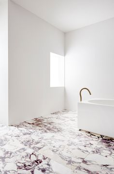 Bold veined rose marble floor in this minimal bathroom design