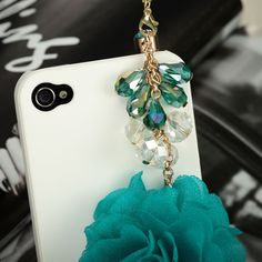 This flower ball 3.5mm headphone plug charm features a 3D chiffon flower ball dangled from a cluster design of dazzling crystal drops. This novelty phone charm effectively protect your devises from dust and water.
