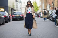 A printed sweater is paired with a navy blue midi skirt, khaki trench coat, and green Céline pumps