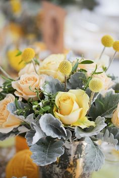 Yellow and pale, pale peach roses with silverly filler.