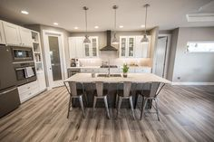 Gorgeous kitchen with painted tundra cabinets, Hanstone - Tranquility counters, Mannington Restoration - Fairhaven - Brushed Taupe flooring, and GE Slate Appliances