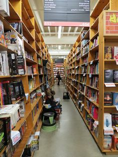 """Two boys in the """"Star Wars / adventure / scary stories/ superheroes / comics aisle of Powell's Books, Portland Oregon"""