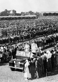 November 25, 1953, as Queen Elizabeth II and the Duke of Edinburgh pass through long lines of schoolchildren at a youth rally to greet the royal couple in Sabina Park, Kingston, Jamaica.