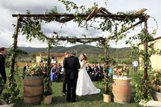 love the use of the olive branches to form a less formal frame, also the barrels. Perhaps add some loosely draped sheer fabric into the mix to soften and add some other color to the largely green background. Il Borro Tuscany Vineyard Wedding on Style Me Pretty