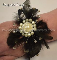 This Chic Wrist Corsage which is handcrafted with  Black Feathers , Silver Diamantes ,Pearl Brooch and created on a Black pearl bracelet. www.designelementflowers.com