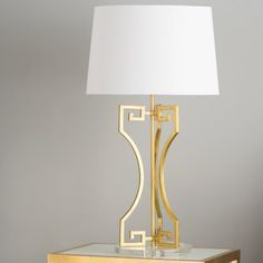 """No room or space is complete without the right lighting. Brimming with chic style, this 31"""" Table Lamp is a must-have addition to your home. Showcasing a distinctive Greek key design, an antiqued gold finish, white empire shade, and clear base, this eye-catching lamp is the perfect accent for any space. Try setting this lovely luminary on a golden nightstand in your master suite or guest room for a warm glow and pop of style. To craft a glamorous aesthetic and complement your lamp, add a..."""