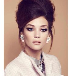 Late 60's-Early 70's pinup like look. Neutral makeup/semi bold eyes. Hair up do. Women's suit.