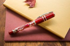 A burgundy and gold inspired flat lay of fountain pens, notebooks, and ink.