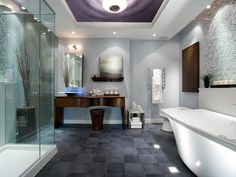 To create a modern, boutique-hotel vibe, Candice injects the bathroom with a palette of grays, blues and pure snow. Elements, like the ceiling mural, stainless steel chain window treatment and gray and white mosaic-tiled wall, are pieces of art while also adding function and personality to the space.