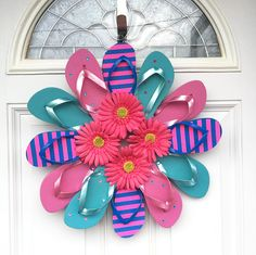 """The new popular summer idea is to make flip flop wreaths! There are so many ways to make them but here are some of my favorites I found! Glue 7 bright colored flip flops together overlapping each other and spell out the letters""""Welcome"""" on each shoe. You will need something for the back such as …"""