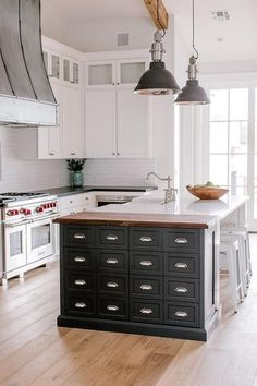 A black apothecary style prep island, accented with polished nickel cup pulls and a wood countertop, is positioned beside a white kitchen island seating three white Tolix stools at a white quartz countertop finished with a farmhouse sink and a polished nickel deck mount faucet.