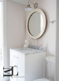 Stunning powder room features walls clad in white and beige dotted wallpaper lined with a small single washstand topped with grey marble…