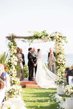 Couple Under Rustic, Floral Chuppah | Photography: Laurie Bailey Photography. Read More:  http://www.insideweddings.com/weddings/classic-california-wedding-with-outdoor-ceremony-indoor-reception/853/