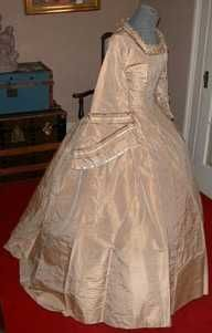 "Civil War Era Wedding Gown  This is an amazing 2 piece ""cafe au lait"" colored silk dress from the Civil War Era, perhaps a wedding dress(?).   The bodice is boned with 10 stays and is fully lined in polished cotton. The center front of the bodice is ""laced"" with a silk cord (decorative only as it is covered over on the inside with a strip of silk) through 24 sets of tiny handstitched eyelets. The neckline is square and is trimmed with ruching of the same silk with a narrow band of cream…"