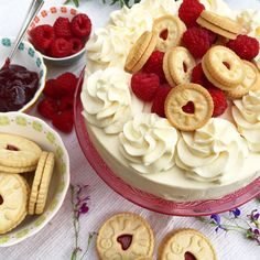 A creamy No-Bake Vanilla and Raspberry Jam Ripple Cheesecake with a Jammie Dodger Base topped with Whipped Cream, Fresh Raspberries and even more Jammie Dodgers. A deliciously fun Jammie Dodgers Ch…
