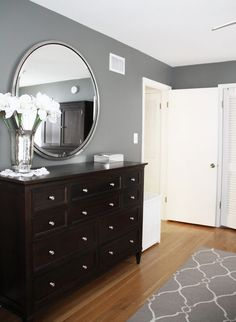 Gray walls, black dresser, silver mirror.