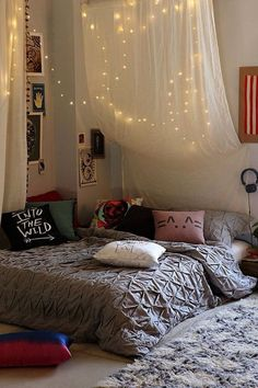 Bedroom with cool throw pillows and a fairy light canopy.