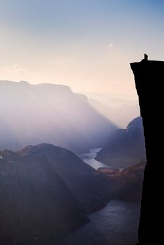 A hiker enjoys the breathtaking views over the Lysefjord from Pulpit Rock (Preikestolen). The rock which overlooks the fjord 604 metres below is one of Norway's most popular natural attractions and is a Norwegian icon.