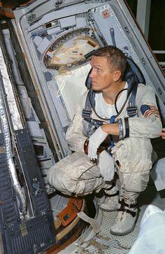 October 25, 1965 – Astronaut Frank Borman looks over the Gemini 7 spacecraft during weight and balance tests conducted in the Pyrotechnic Installation Building, Merritt Island, Kennedy Space Center, Florida. (NASA)