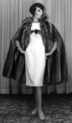 June 26, 1964 A model poses in a design by Anne Fogarty at a press preview fall fashion show in New York City. The slim, sleeveless white wool dress with a high waist is emphasized by a satin pull-through bow. The bulky cape coat is raccoon. The week-long program is sponsored by about 40 American fashion houses.
