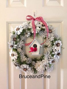 This unique Winter wreath in serene colors of gray, blue and white will compliment your modern decor. A silver glitter spray and touch of red pops through to celebrate the season. These hand painted pine cones are wired and sprayed with a clear acrylic coat for lasting durability. *