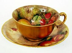 A Royal Worcester cabinet cup and saucer hand-painted with fruit and signed H. Ayrton, black back-stamp, date code for 1952.