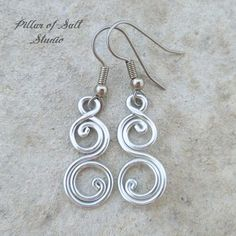 • Aluminum • Stainless steel ear wires • Lightweight • Length: 1 5/8 from the piercing Handmade aluminum wire spiral earrings. Aluminum is a wonderful material for earrings because it is lightweight and wont tarnish like silver. And shiny! These earrings have been hammered and tumbled for greater strength and shine, however aluminum is a soft metal and will bend more easily than copper or silver so care should be taken to avoid situations where they could get bend (such as a pocket or p...