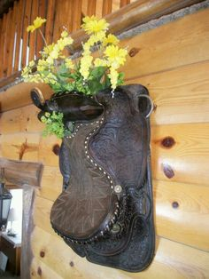 Old saddle now holds flowers!great idea for my bunk house bedroom:)