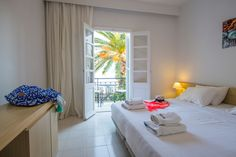 Pamper yourself in the all-white rooms while outside the traditional wooden windows. All White Room, White Rooms, Wooden Windows, Shades Of Beige, Beach Hotels, Traditional, Mansions, Bed, Holidays