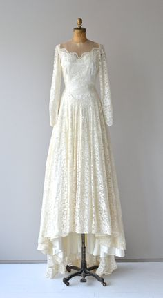 Vintage classic 1950s ivory lace wedding gown with net lace illusion neckline, long sheer lace sleeves, princess seaming, long buttons back closure, fitted waist, button sleeves and long extending lace train.