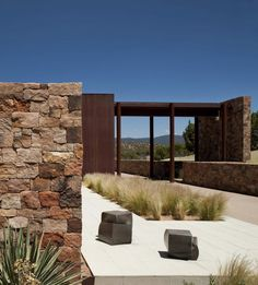 Casa Valle Escondido / Bucchieri Architects. Stone wall and rusted steel with ornamental grasses