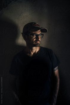 Serious Man with Cap in the Shadows by VICTOR TORRES for Stocksy United