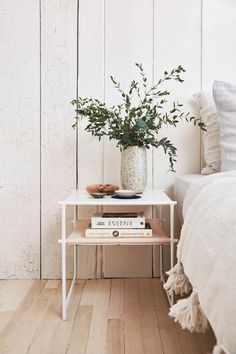 simple nightstand with vase, white on white, tassled throw, wooden panelling