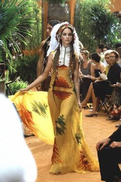 * John Galliano for Dior Fall/Winter 1998 Orient Express couture collection Model wearing a Native American inspired evening ensemble comprised of yellow chiffon accordion-pleated dress with appliqueed design in shades of red and green, feather headdress, and beaded bib necklace. Circa July 1998 © Guy Marineau