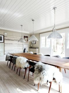modern dining room with mid century modern danish long table, flokati throws on chairs, shell pendant lights, paneled wall texture and wood floors