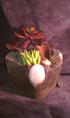 'Plowing Stone' - You are viewing a TufaGems hypertufa planter/container artistically handcrafted with a beautifully rusted piece of metal from an old farm implement. The metal piece is clasping polished white river rocks and there are two addl polished white river rocks inset into the planter itself.