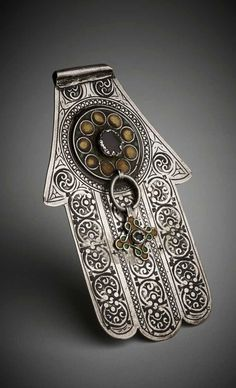 Silver 'Hand of Fatima' or 'khamsa' (meaning 'five') amuletic pendant in the shape of a hand. Decorated with a raised circular roundel affixed near the top comprising yellow enamelled circles set within twisted silver wire frames and surrounded by remnant Antique Silver, Moroccan Jewelry, Hamsa Necklace, Hand Of Fatima, Jewish Art, Hamsa Hand, Tribal Jewelry, Jewelry Art, Fatima Hand