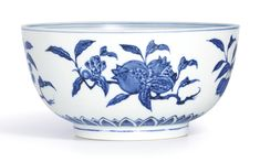 AN EXTREMELY RARE BLUE AND WHITE 'FRUIT' BOWL MING DYNASTY, YONGLE PERIOD the deep rounded sides rising from a short foot, vividly painted on the exterior with detached fruiting branches of peach, crabapple, pomegranate and longan, above a band of overlapping petals encircling the foot, the interior decorated with a roundel enclosing a chrysanthemum spray, the cobalt of an attractive blue tone with pronounced characteristic 'heaping and piling' effect
