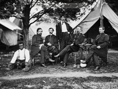 Group portrait showing Brigadier General Napoleon Bonaparte McLaughlen (seated second from right) and other soldiers in front of tent. An African American man is sitting at far left with a small dog. Date Created/Published: 1865 July.