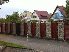 Eine Kombination aus Gabionen und Holzelementen wird wirkungsvoll als Sichtschutz und Gartenzaun eingesetzt.