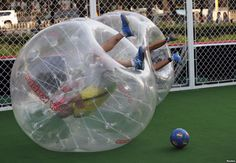 Players partially encased in giant plastic inflatable balls roll over on the ground, their legs in the air, during their bubble soccer match...