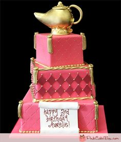 Genie Lamp Birthday Cake (2079) - We created this three tier square cake for a 3 year-old's birthday. The party was Arabian themed and at the top of the cake we included a gold 3D sculpted genie lamp. The top and bottom tiers were covered with quilted fuchsia and decorated with gold piped dots and gold tassels.