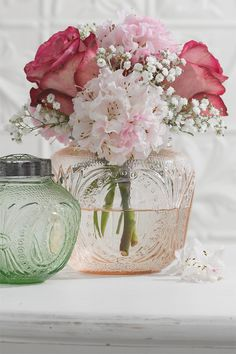 The beauty of pale pink and green pressed glass bottles with flowers.