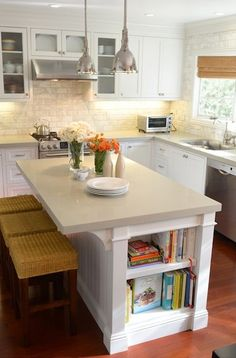 L shaped kitchen, shaker cabinets, gray quartz countertop, beveled marble subway tile backsplash. Restoration Hardware Benson Pendants over white kitchen island with corbels and built-in bookcase filled with cookbooks.