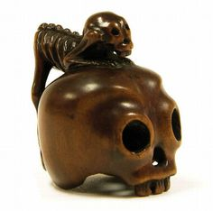 A boxwood netsuke, early 19th century, unsigned. A macabre study of a skeletal monkey crouching over the top of a human skull. All details lightly worn with a good patina. Old English collection. Height 4.4 cm