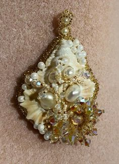 Sea shell bead embroidery with center cut shell slice, embedded with fresh water pearls. The sea anemone is made with a glass opal center. Some light beaded coral to finish the pendant.